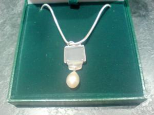 A pendant made from jade and pearl