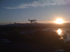 a plane landing against the setting sun